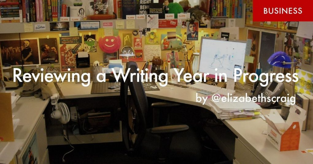 "A desk with cube walls completely covered with colorful papers and posters is in the background and the foreground has the post title, ""Reviewing the Writing Year in Progress"" superimposed on it."