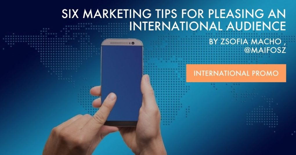"Man's hands hold a cell in front of a digital map of the world, while the post title, ""6 Marketing Tips for Pleasing an International Audience by Zsofia Macho is superimposed on the top."